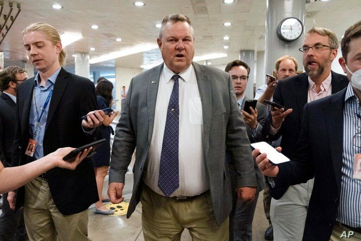 Sen. Jon Tester, D-Mont., talks to reporters as he walks to the Senate chamber ahead of a test vote scheduled by Democratic…